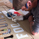 Mike hand painting the sign for Hound Dog + Cat